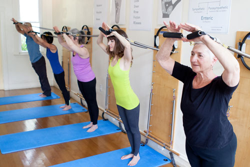 Students of various ages using pilates springboard equipment.