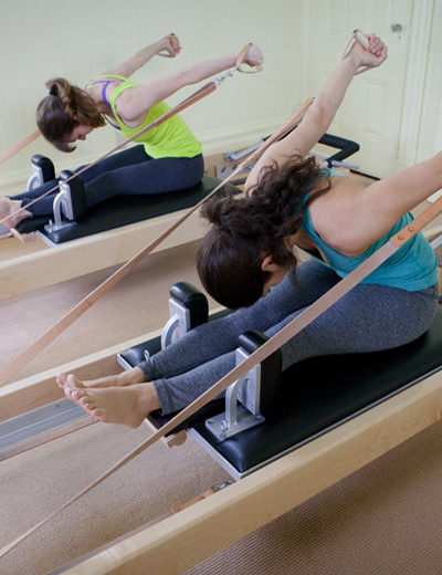 Two women exercising on Pilates equipment.