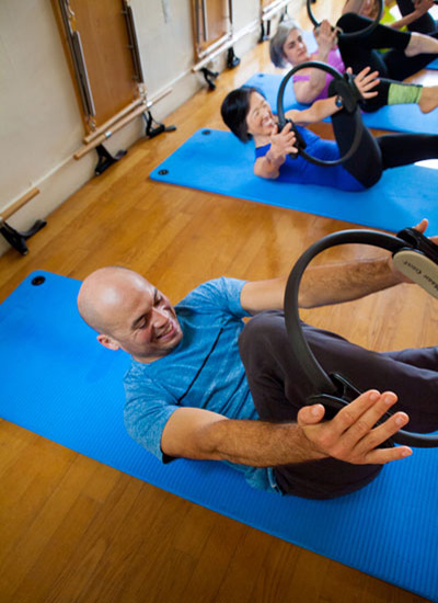 Man exercises with pilates ring in a group pilates mat class.