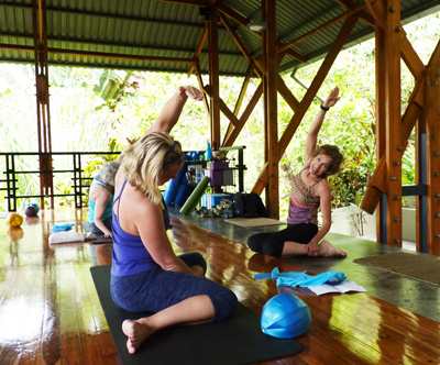 Teacher and two students exercising at open air studio in Costa Rica.