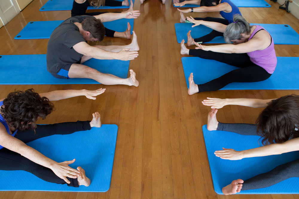 Students exercise in a group pilates mat class at Sanchez Street Studio in Noe Valley.