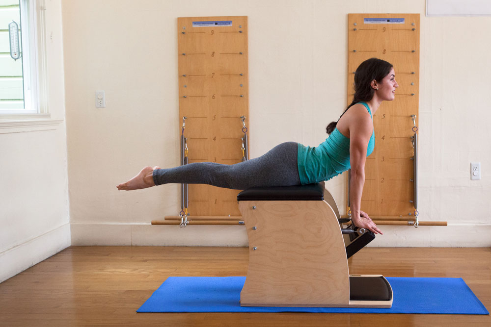Woman doing a back bend on a piece of pilates equipment.