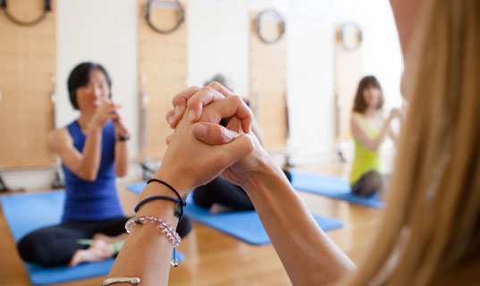 Clasped hands in pilates class.