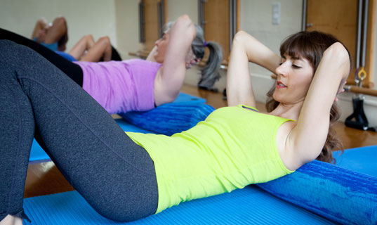 Women doing stomach exercises in Pilates mat class.